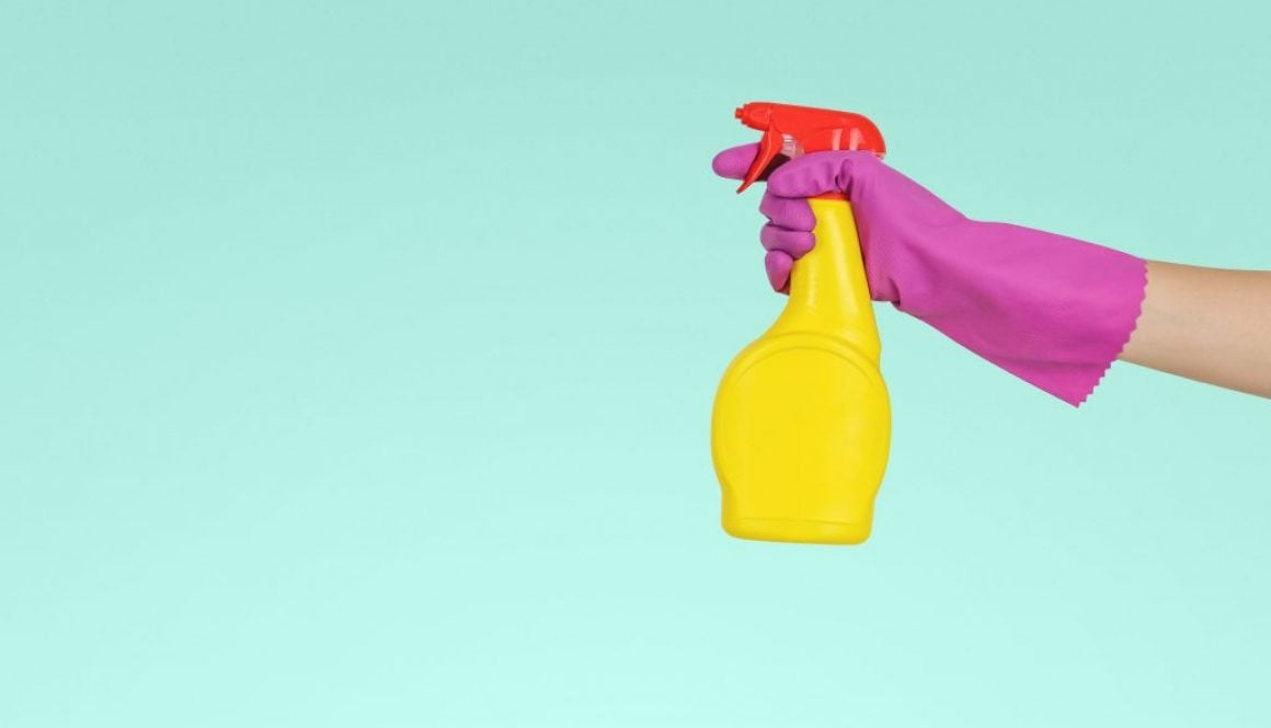 Spray cleaner held by person wearing rubber glove
